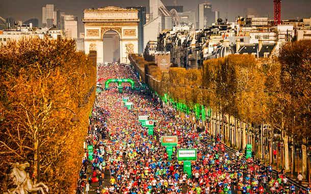 Corredores de la Maratón de París pasando por Campos Elíseos y Arco de Triunfo